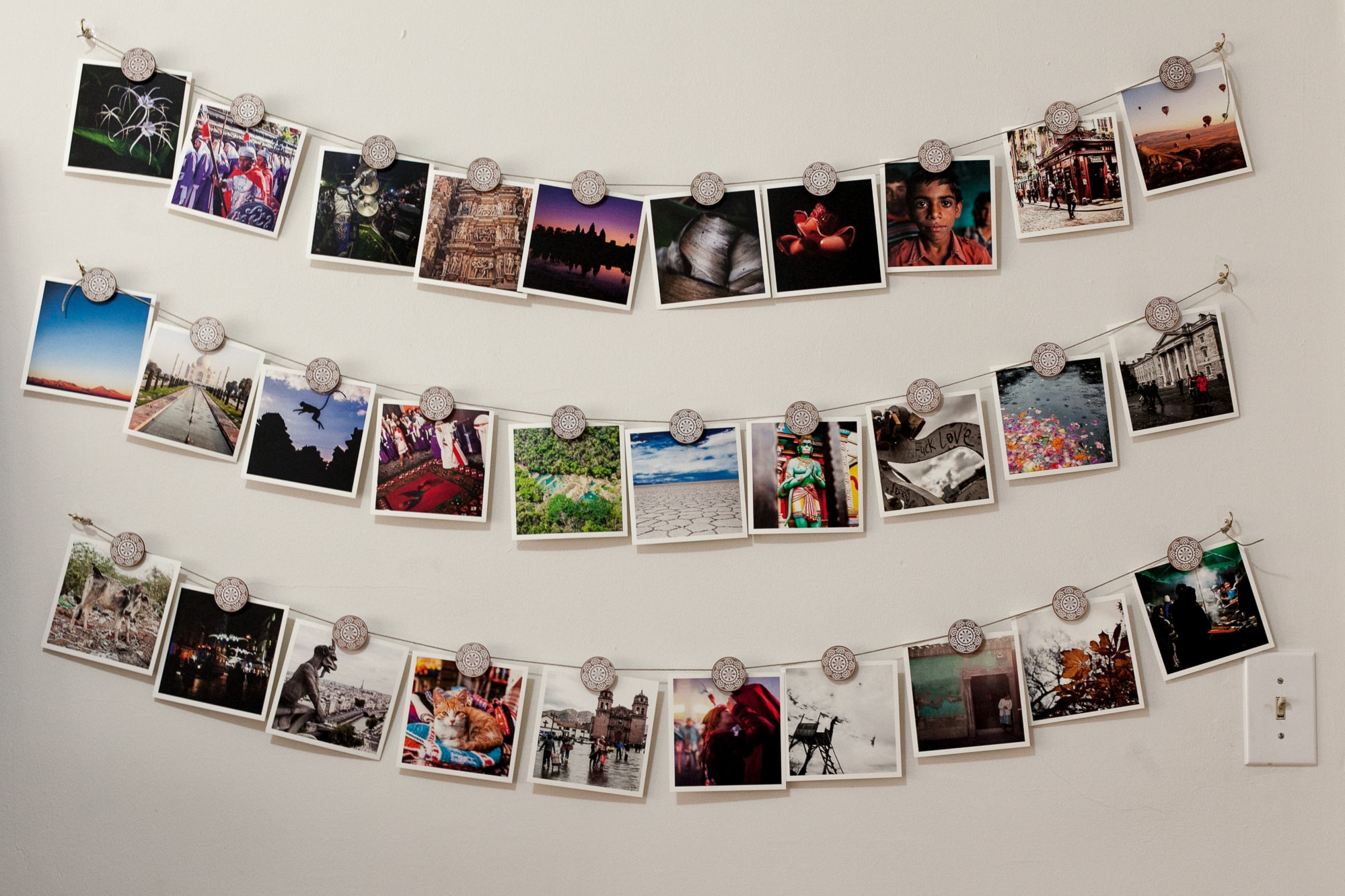 Artifact Uprising square prints of travel photos hanging from Urban Outfitters Henna Medallion Photo Clip Set.