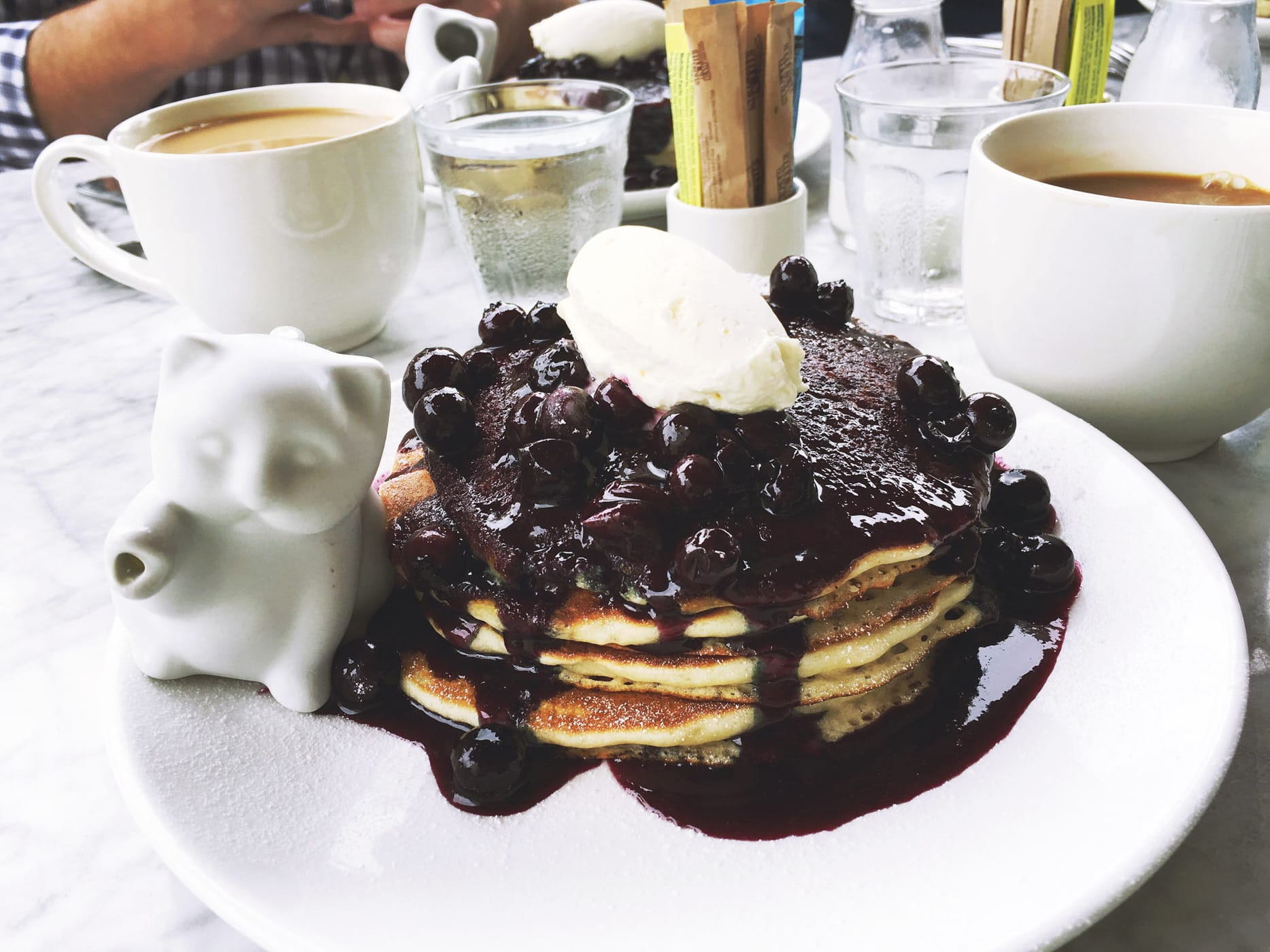 Buttermilk pancakes with blueberry maple compote, crème fraiche, and a kitten syrup dispenser at Launderette in Austin, Texas.