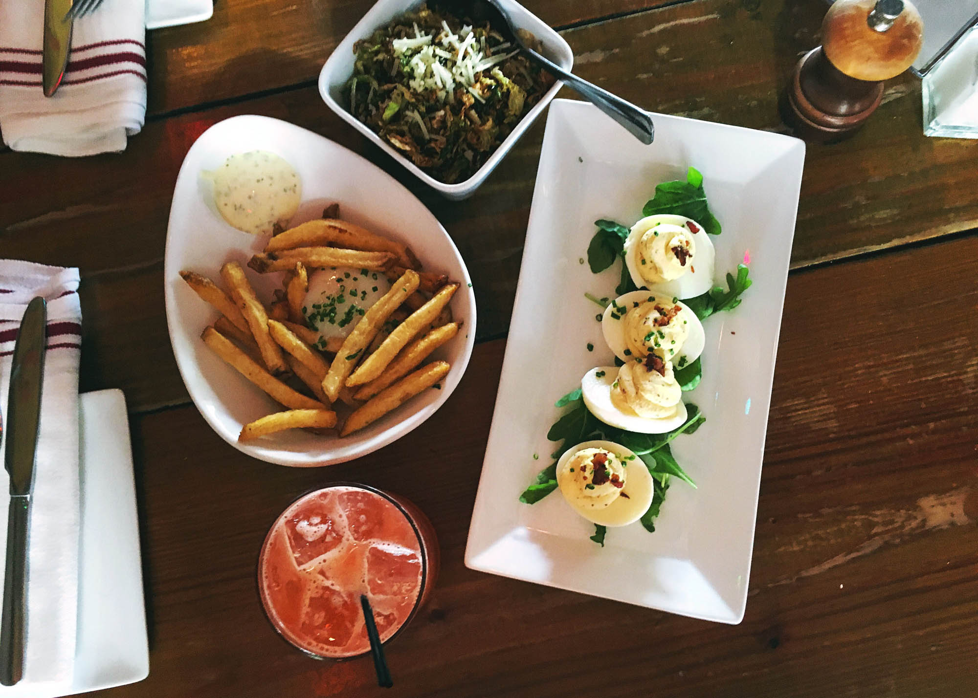 Truffled deviled eggs, duck fat fries, and crispy brussels sprout leaves at Salty Sow in Austin, Texas.