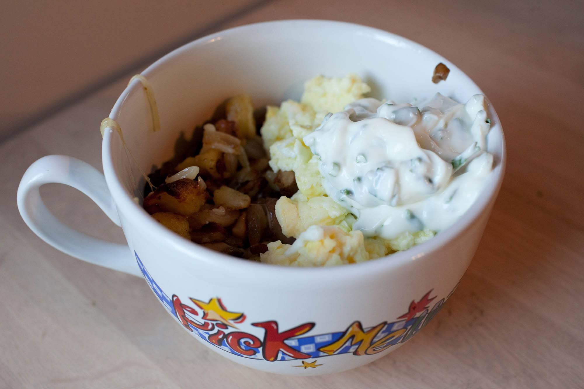 Home fries with mushrooms, onions, and cheese topped with scrambled eggs and chive sour cream.
