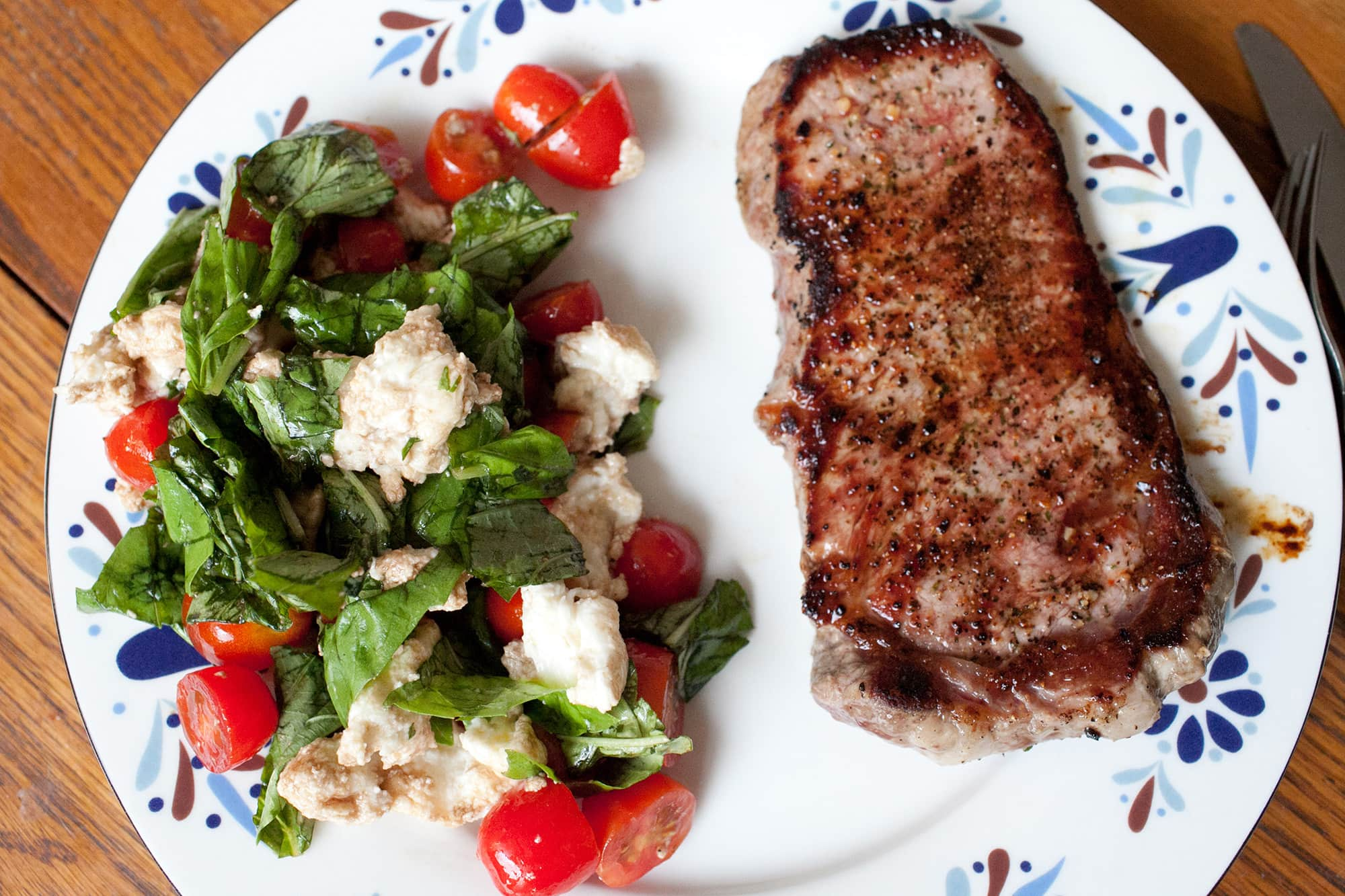 Rib eye steak and a caprese salad.