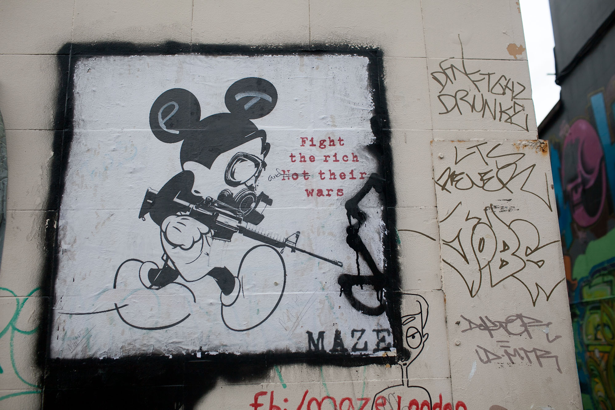 Fight the rich, not their wars. Mickey Mouse with a gas mask and gun by MAZE | Brick Lane Street Art in London. | Street Art at Brick Lane in London, England.