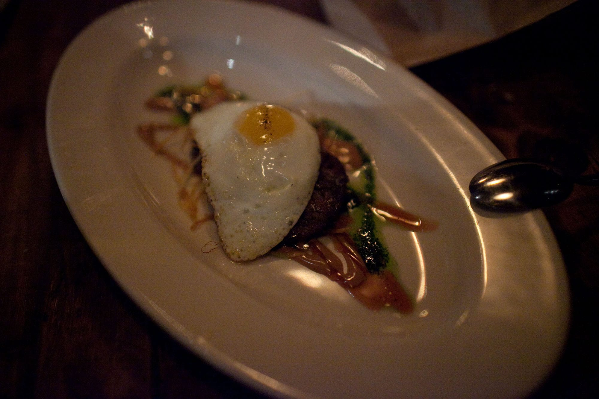 Girl and the Goat - Wood oven roasted pig face with sunny side egg, tamarind, cilantro, and potato stix.