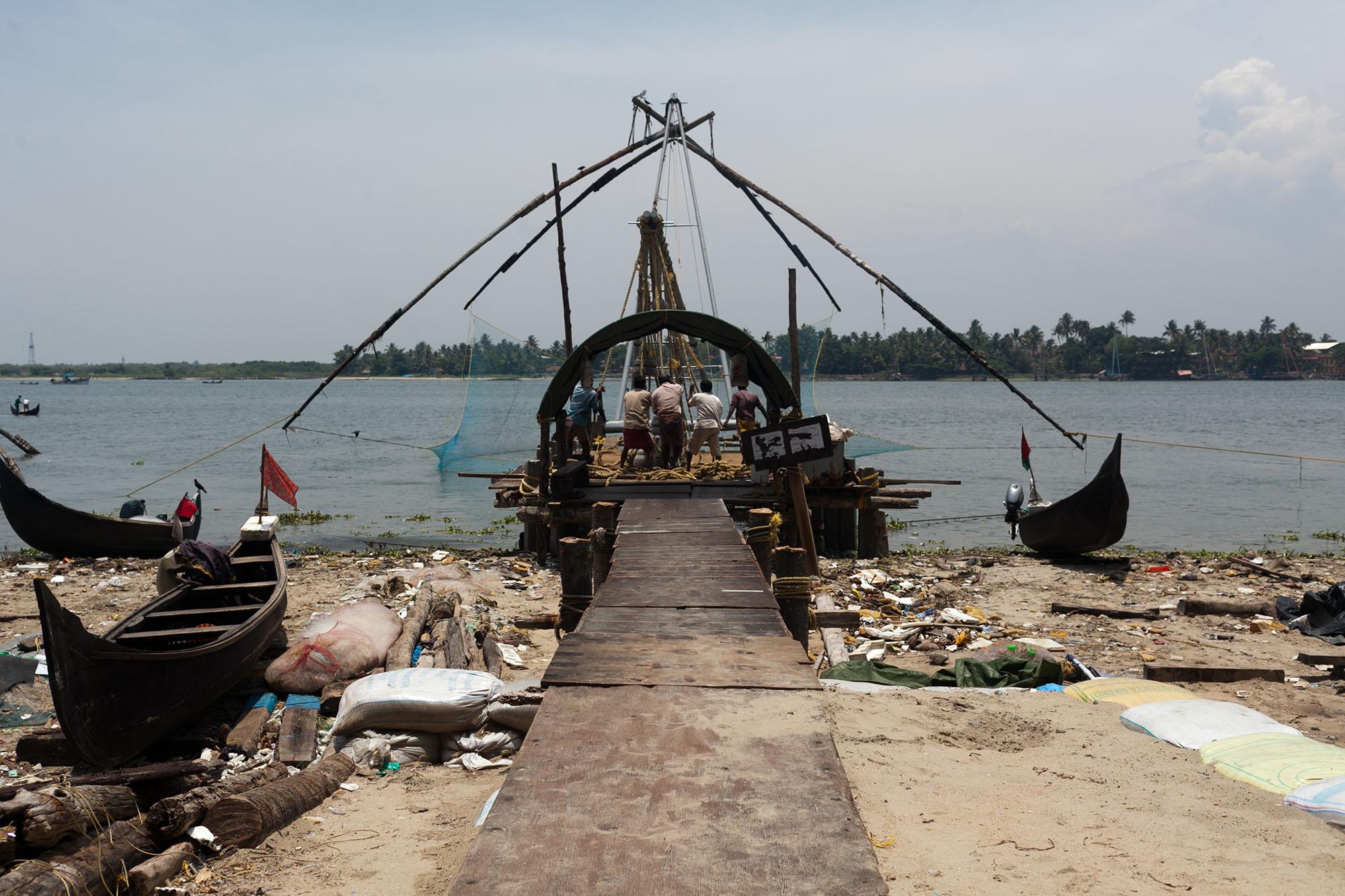 Fishermen fishing with their wooden fishing mechanisms in Kochi, India (Cochin) in Kerala.