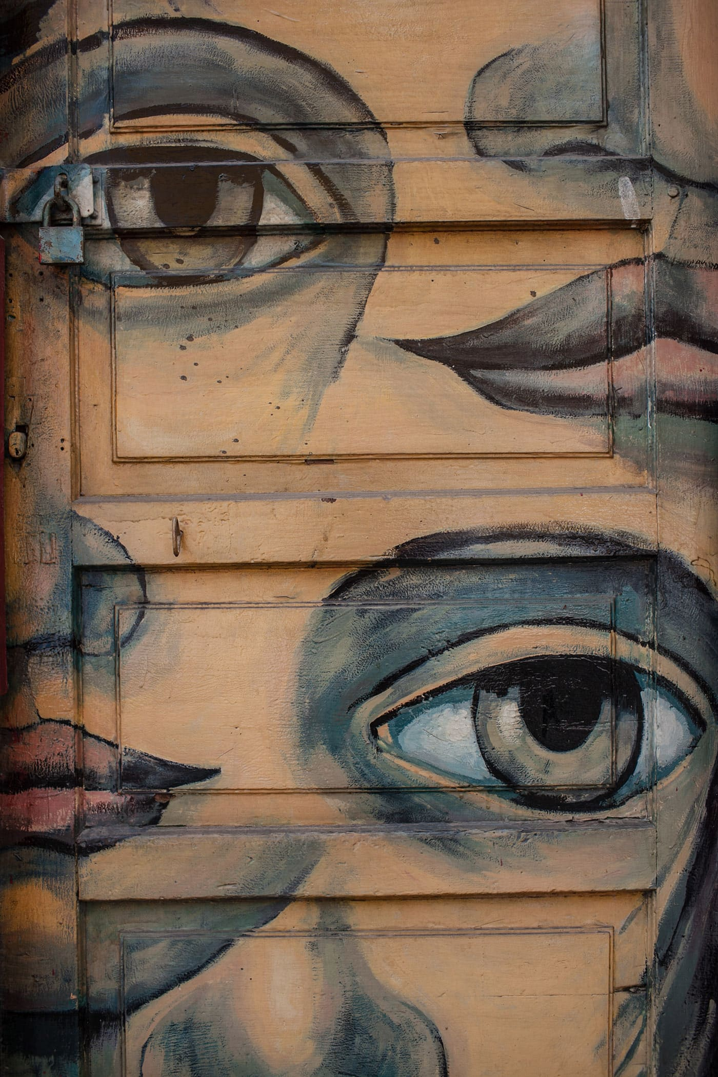 Best Street Art in Valparaiso, Chile - faces with large eyes, noses, and lips on a door