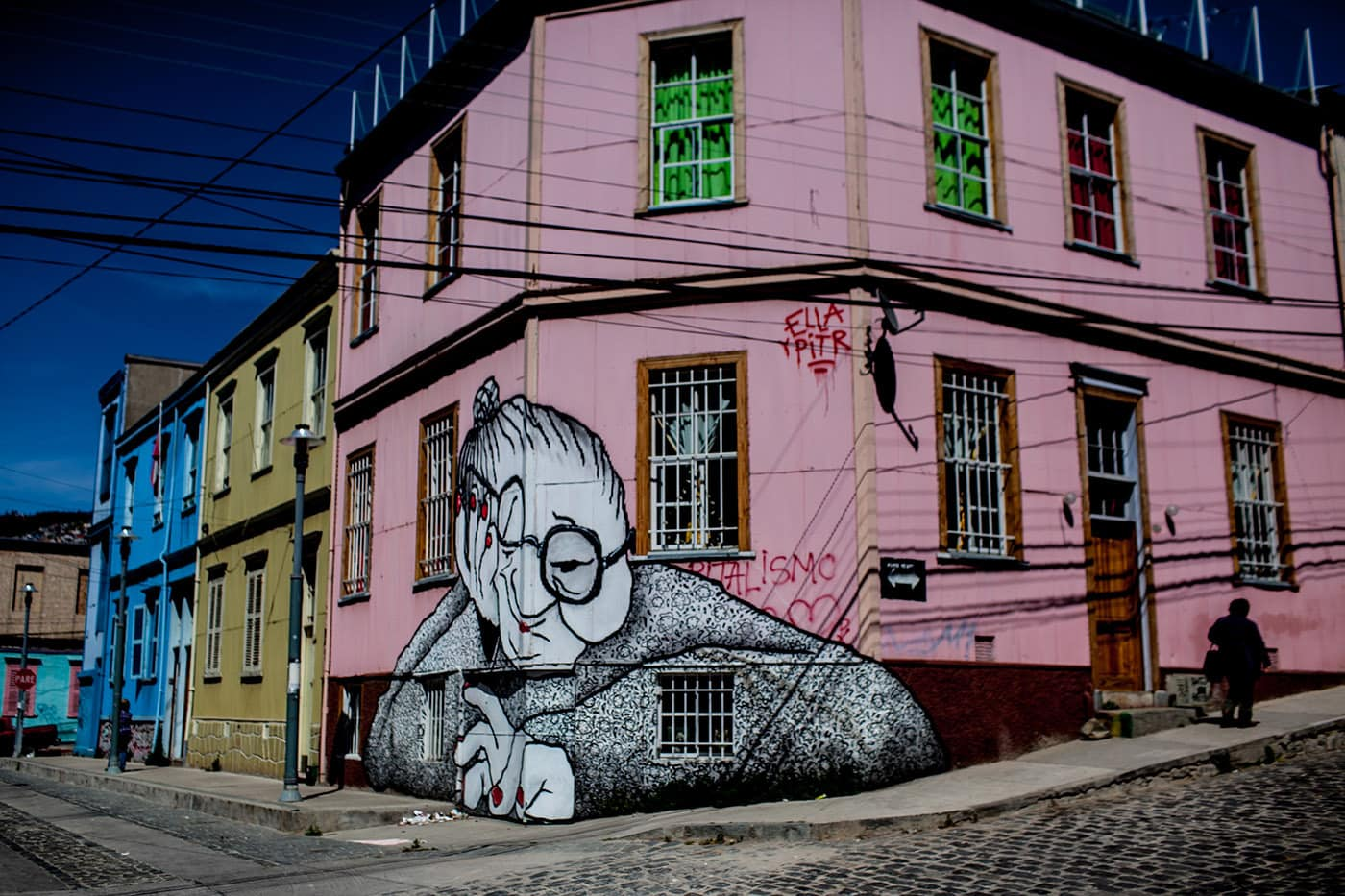 Best Street Art in Valparaiso, Chile - old woman in glasses on a pink building