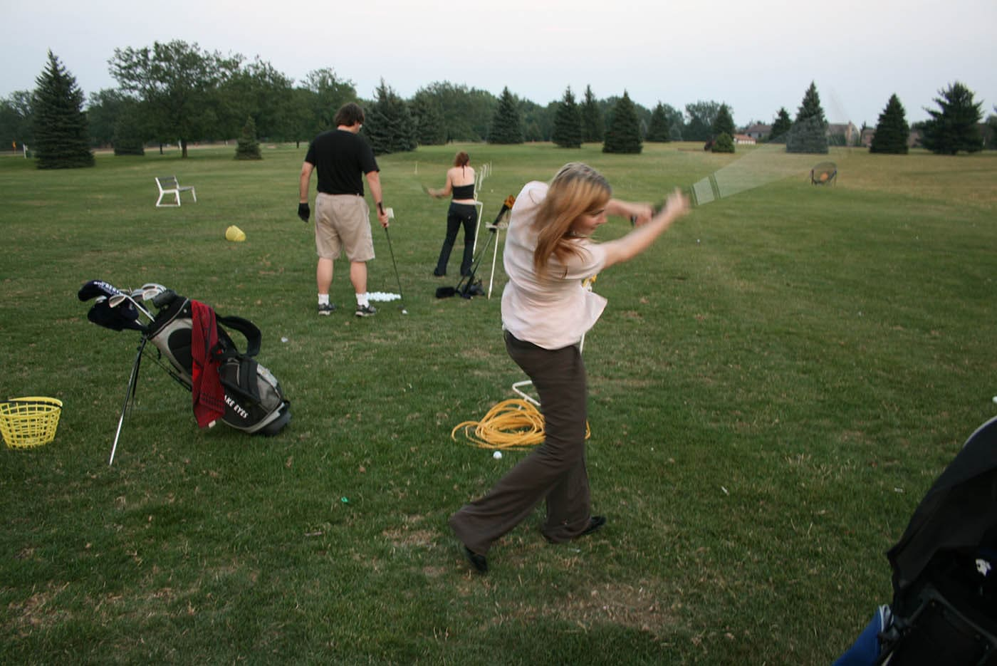 Learning to golf at the driving range.