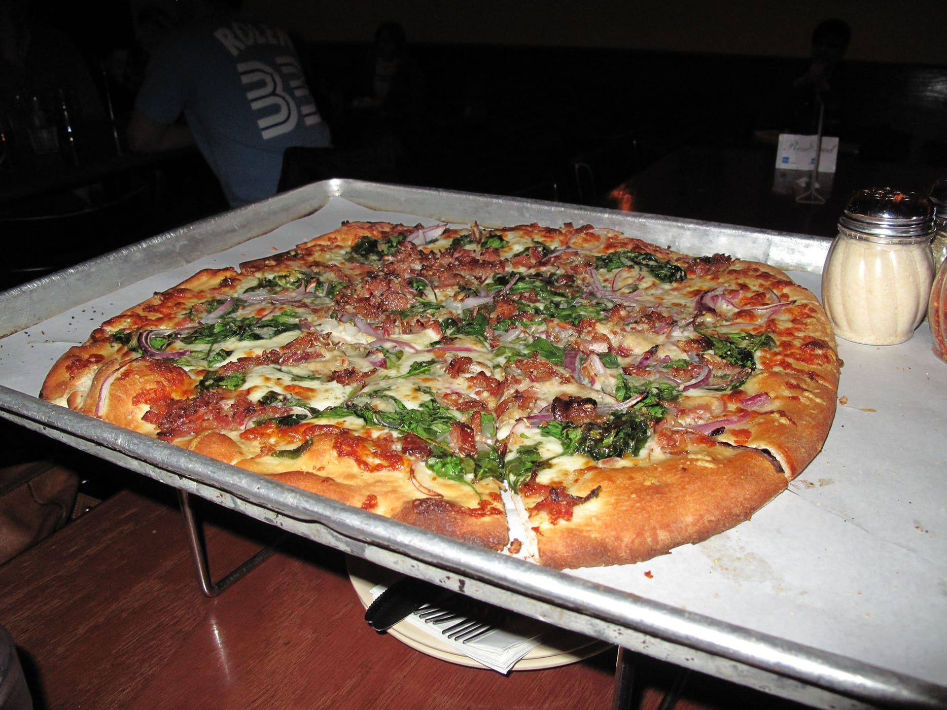 Pizza with spinach, red onions, and bacon, from Piece Brewery and Pizzeria in Chicago
