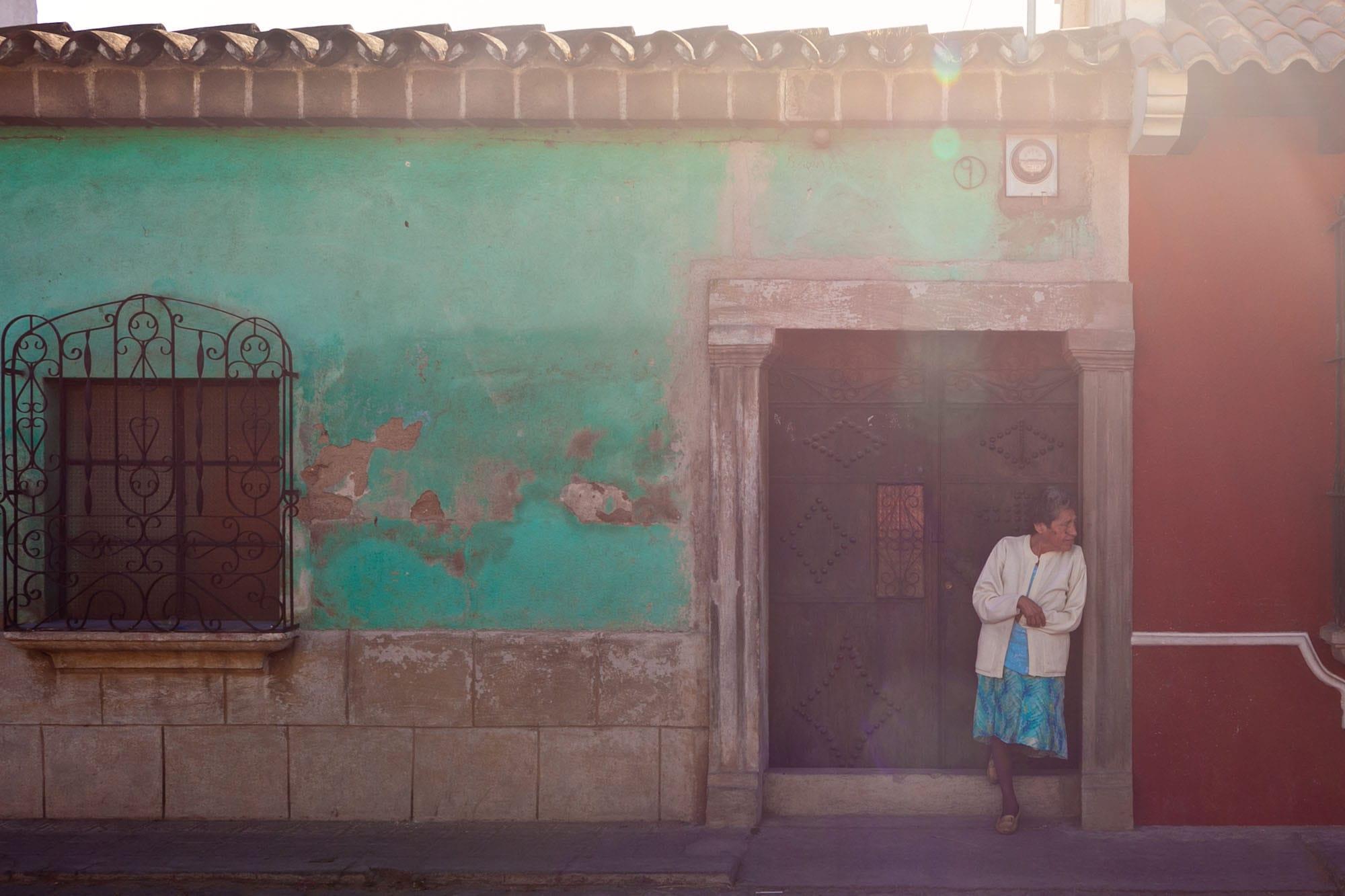 A woman stands by a door in Antigua, Guatemala