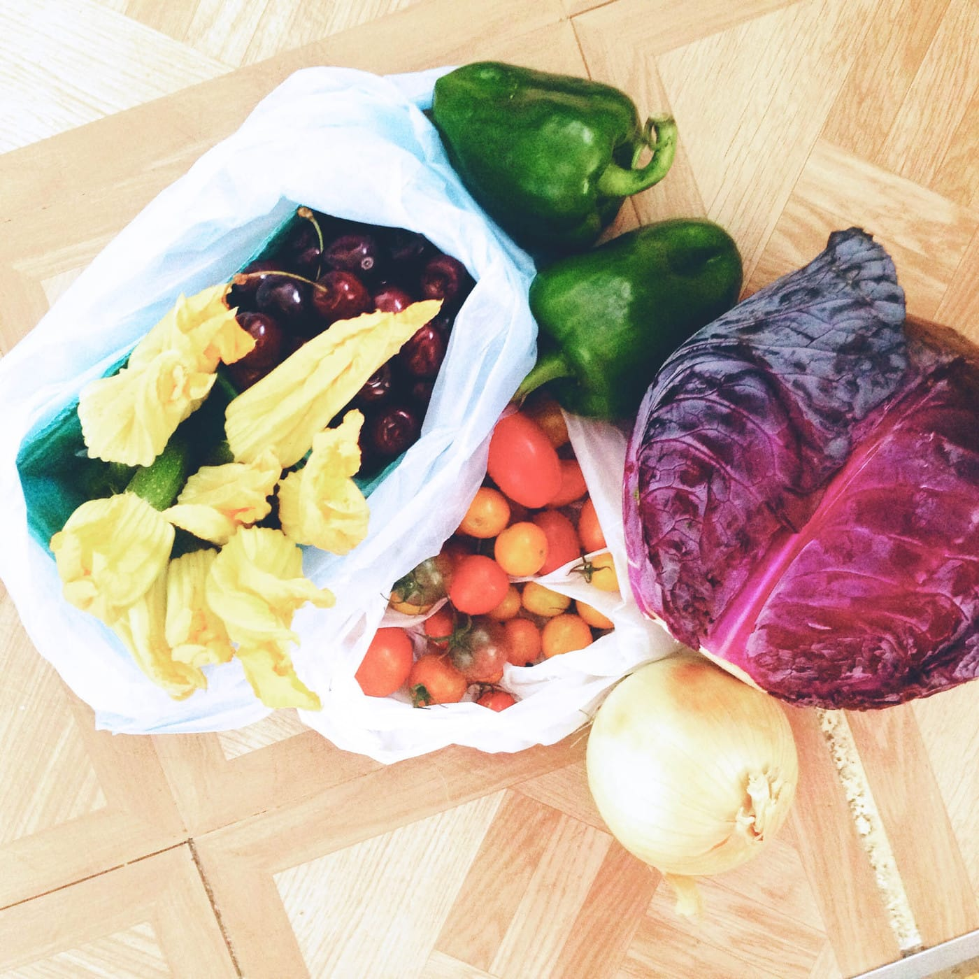 Peppers, cabbage, tomatoes, onion, cherries, and squash blossoms from the Chicago Lincoln Square Farmers Market.