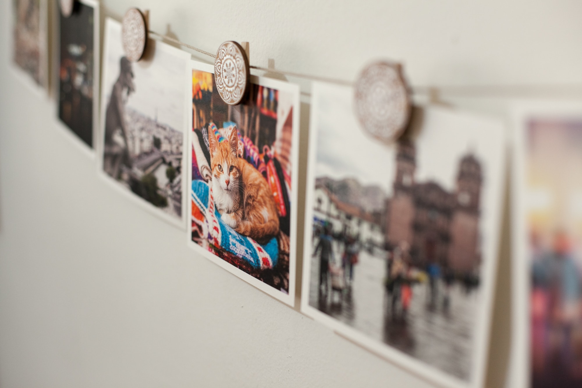 Wall of Travel Photos - Artifact Uprising square prints of travel photos hanging from Urban Outfitters Henna Medallion Photo Clip Set.