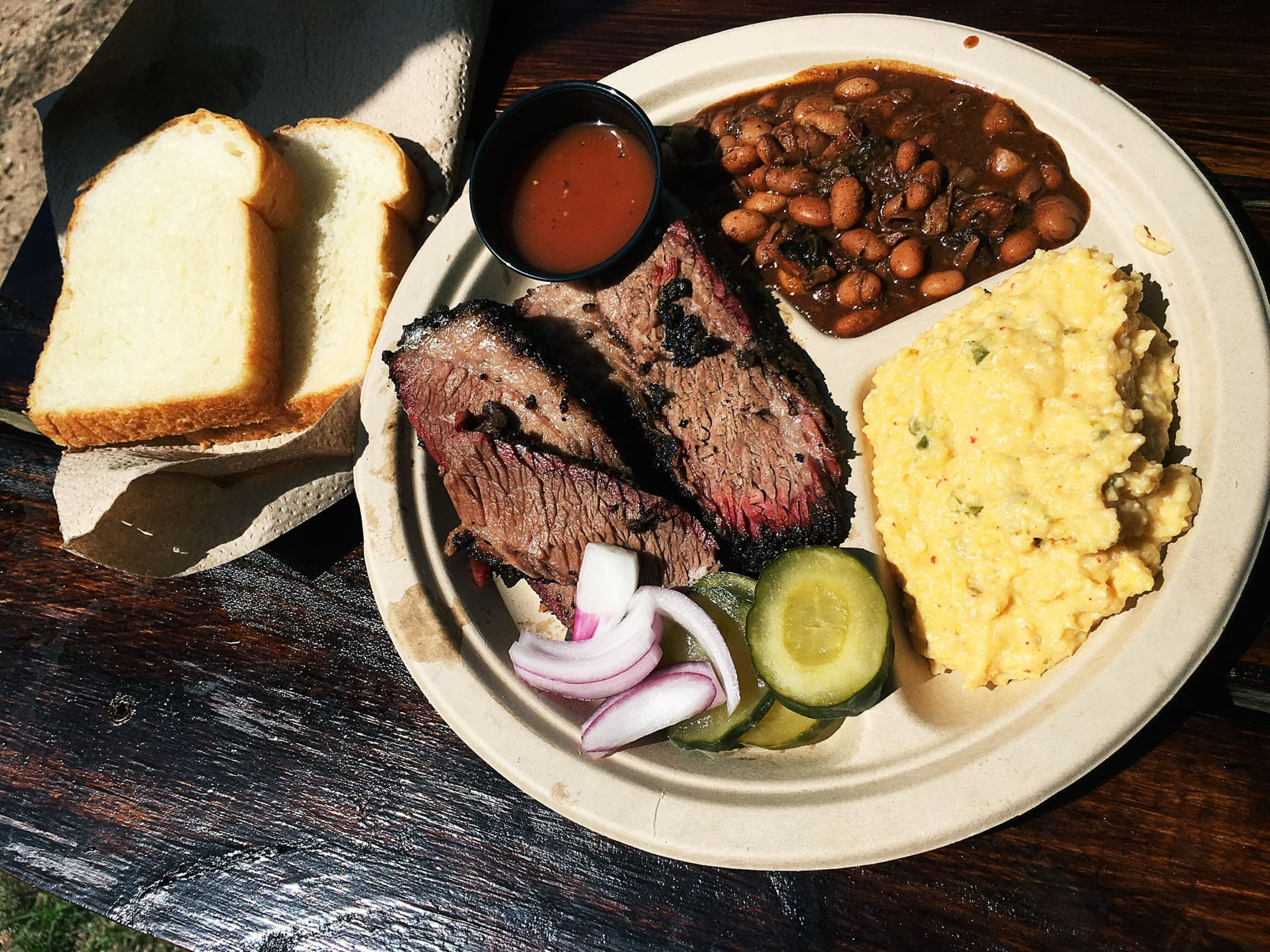 Brisket plate with jalapeno cheese grits and campfire chili beans at Micklethwait Craft Meats food truck in Austin, Texas.