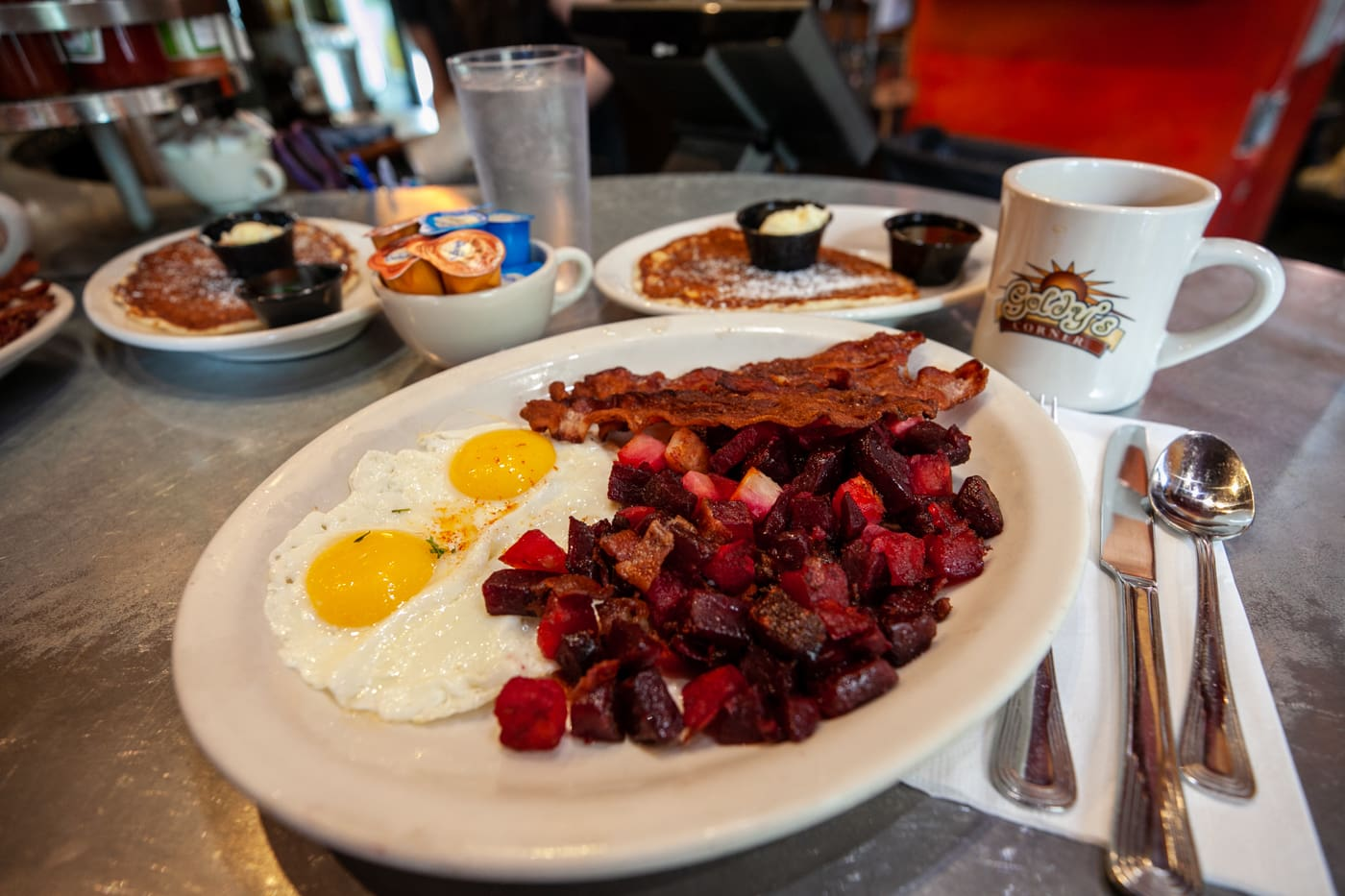 Create-your-own breakfast combo I had at Goldy's Breakfast Bistro in Boise, Idaho: two eggs (sunny side up), bacon, red flannel hash (potatoes, beets, and... more bacon), a blueberry pancake, and, of course, some coffee to fuel my morning. It was so good.⁠